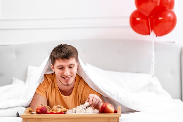 ベッドでの朝食とミディアムショット男