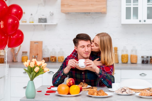 Среднего выстрела женщина целует мужчину в щеку