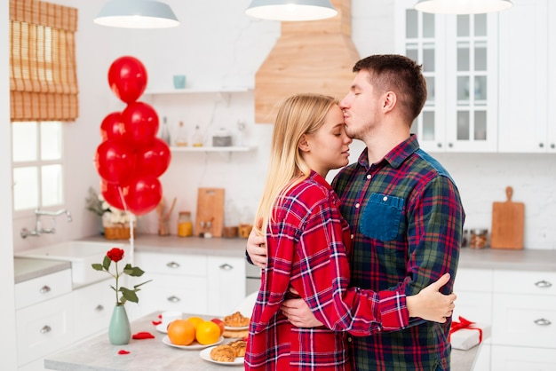 Вид сбоку мужчина целует женщину в лоб