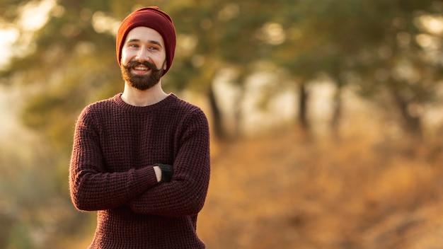 Бородатый мужчина позирует на природе