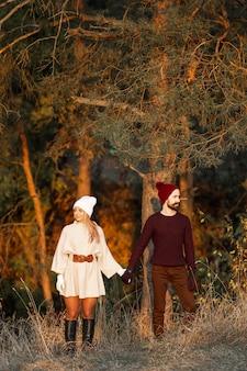 Мужчина и женщина, держась за руки рядом с деревьями