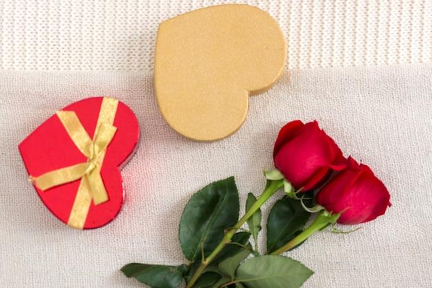 Вид сверху розы и коробка конфет в форме сердца в постели