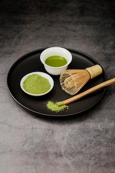 カップに抹茶とプレートに竹の泡立て器