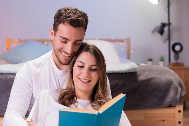 彼らの寝室で読んでいるカップル