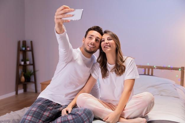 Счастливая пара в постели, принимая селфи