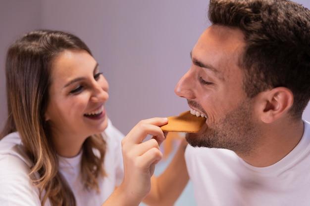 ベッドで朝食を食べる若いカップル