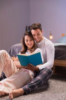 若いカップルがベッドで一緒に読んで