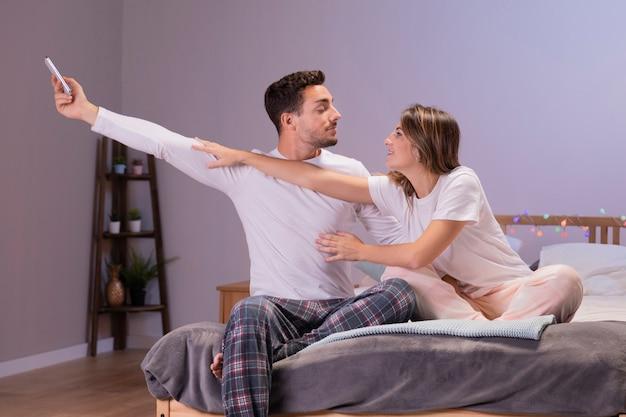Молодая пара весело в спальне