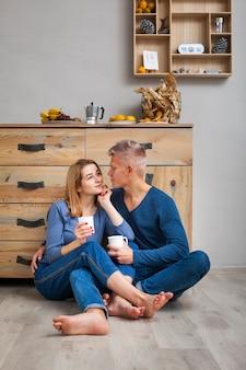 床にコーヒーのカップを持っているカップル
