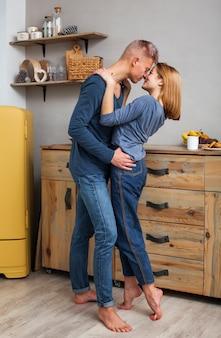 素敵なカップルがキッチンで楽しんで
