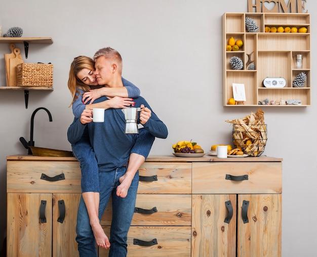 キッチンで抱き締めるロングショットカップル