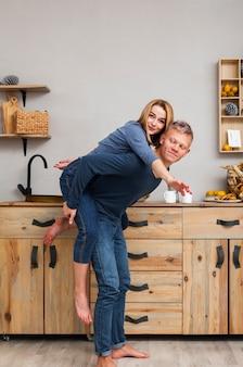 Мужчина несет свою девушку на спине на кухне