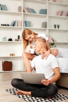 かわいいカップルが自分のラップトップで映画を見て