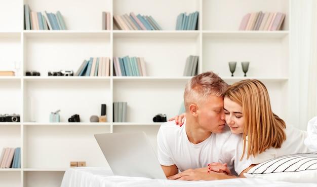 Женщина и мужчина отдыхают с ноутбуком в постели