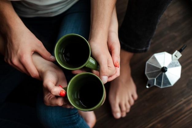 トップビューの男性と女性のコーヒーカップを保持しています。