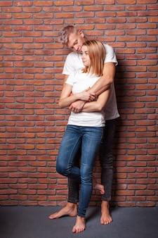 素敵なボーイフレンドとガールフレンドのレンガの壁でポーズの時間を過ごす