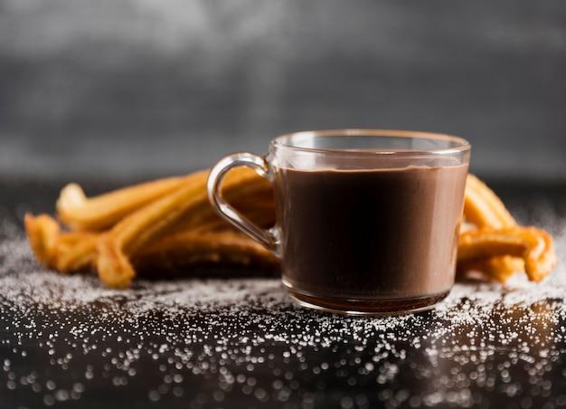 Вид спереди прозрачной чашки растопленного шоколада и чурроса