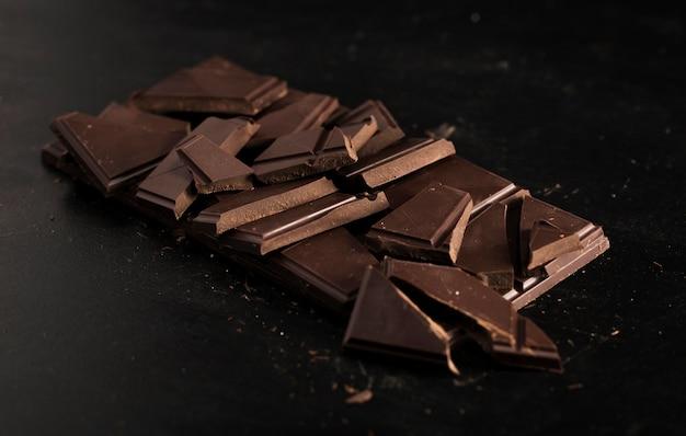 Разбитая таблетка шоколада на черном фоне