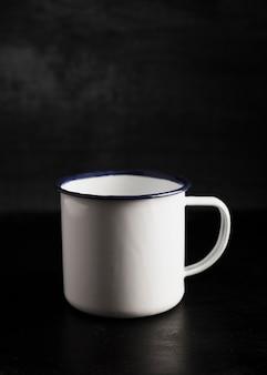 黒い背景に正面白いマグカップ