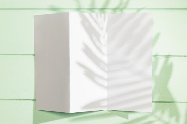 折り畳まれた紙のコピースペースと葉の影