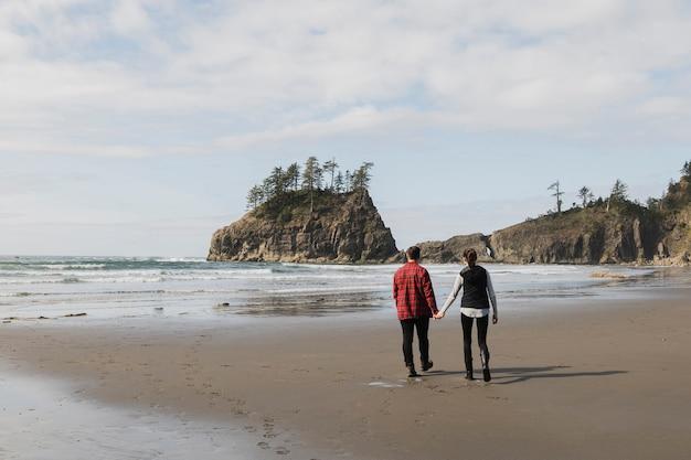 海岸で手を繋いでいるカップルの背面図