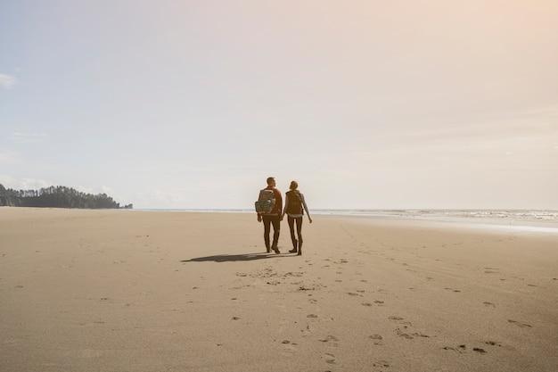 カップルが手を繋いでいるとビーチの上を歩いて