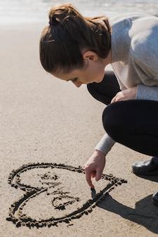 濡れた砂の上の心を作る女性