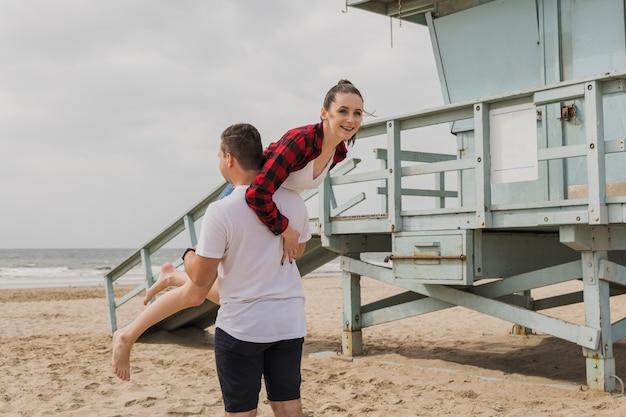 ビーチで女性を運ぶ男