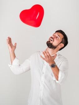 Человек играет с воздушным шаром валентинок