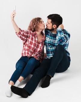 Целующаяся пара, делающая селфи для валентинок