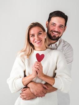 Пара позирует и держит сердце и улыбается