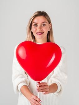 幸せな女がバレンタイン用のバルーンでポーズ