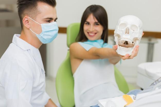 Пациент держит череп у стоматолога