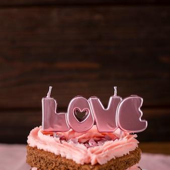 キャンドルでハート形のケーキのスライスのクローズアップ