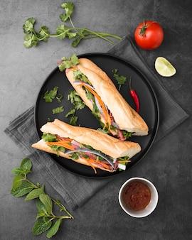 ソースとプレートに新鮮なサンドイッチのフラットレイアウト
