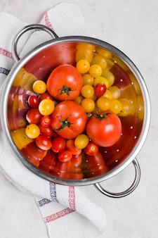 Плоская кладка различных помидоров в миску
