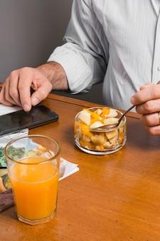 ジュースと健康食品のグラスを持つ男の高角