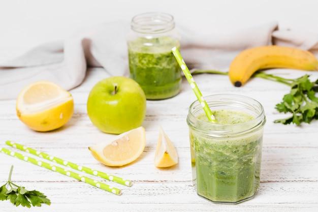 リンゴとレモンのスライスと健康的なスムージーの瓶