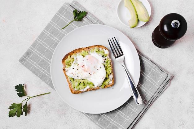 Яйцо с авокадо тост на тарелке