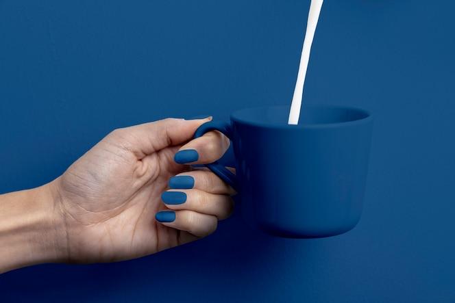 Женская рука держит чашку молока