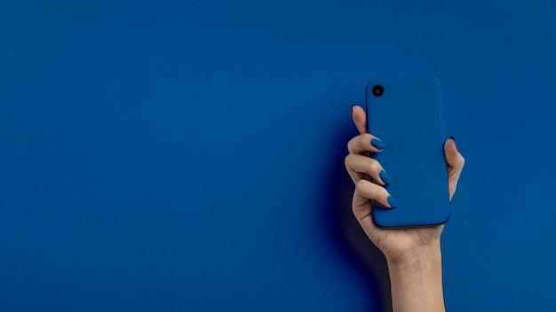 色の背景上の携帯電話を持っている女性の手