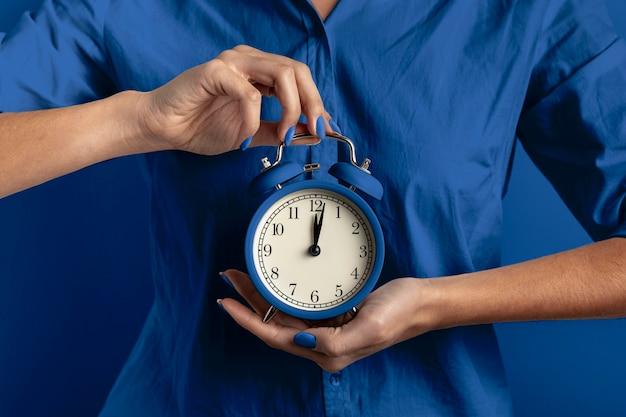古典的な青い色の時計を保持している女性