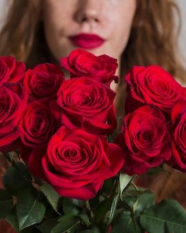 Крупным планом женщина, держащая букет роз