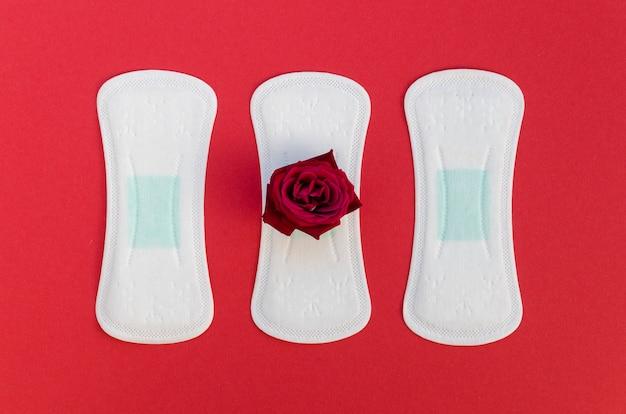 赤の背景に赤いバラとフラットレイアウトパッド