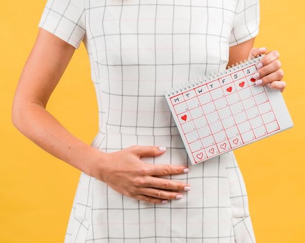 月経から胃けいれんを持つ白いドレスを着た女性