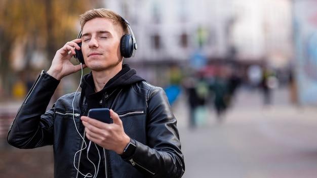 コピースペースとヘッドフォンで音楽を聴く若い男
