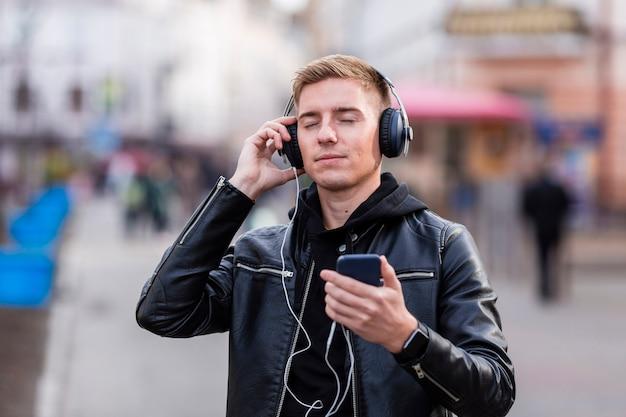 目を閉じて音楽を聴く若い男
