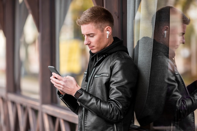 外のイヤホンで音楽を聴く横に若い男