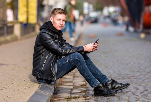 外のイヤホンで音楽を聴く若い男
