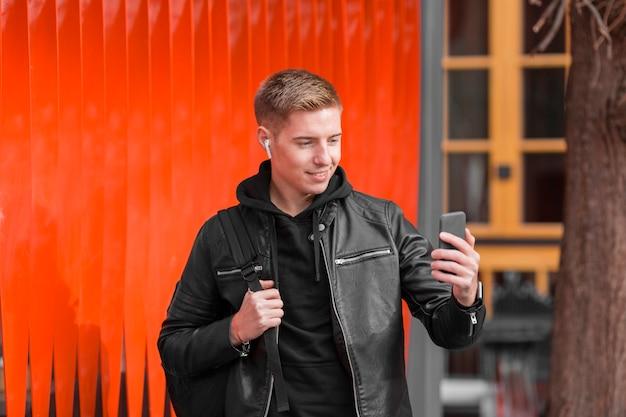外のイヤホンで音楽を聴く正面若い男